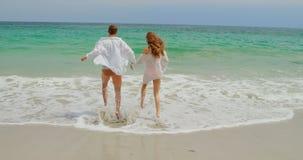 Ideia traseira dos pares caucasianos que correm na praia 4k video estoque
