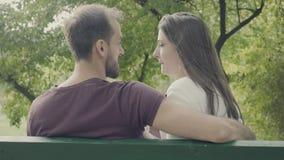 Ideia traseira dos pares em um banco no parque video estoque