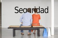 Ideia traseira dos pares que leem o seguridad espanhol do texto (segurança) e que contemplam o imagens de stock