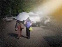 Ideia traseira dos pares sob o guarda-chuva na noite contra o ônibus de dois andares em Tailândia Fotografia de Stock