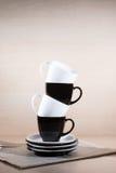 Ideia vertical de estar copos preto e branco na pilha das placas no jornal Imagem de Stock