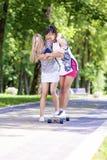 Ideias do estilo de vida do adolescente Duas amigas adolescentes que têm o divertimento Longboard de patinagem no parque fora Fotos de Stock Royalty Free