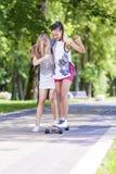 Ideias e conceitos do estilo de vida do adolescente Duas amigas adolescentes que têm o divertimento Longboard de patinagem no par Imagens de Stock