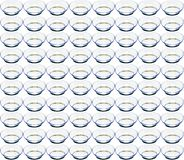 Identical contact lenses with a glare from the illuminator on a white background royalty free stock photography