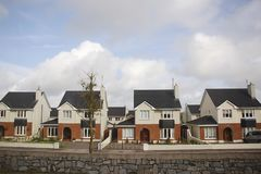 Identical cottages in a cozy suburb. Identical tricolor cottages in a cozy suburb, municipal district densely built over, economy class housing, Ireland stock image