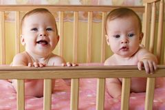Identical twin babies. Portrait of happy and inquisitive identical twin baby girls in cot. Photo of same baby in montage Royalty Free Stock Photos