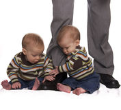 Identical twin baby boys holding dads legs Royalty Free Stock Photography