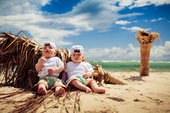 Identical twin boys relaxing on a beach Royalty Free Stock Photos