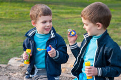 Identical twin brothers blow soap bubbles. Four year old identical twin boys in the meadow. They blow soap bubbles. They sit on the log Royalty Free Stock Photo