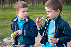 Identical twin brothers blow soap bubbles. Four year old identical twin boys in the meadow. They blow soap bubbles. They sit on the logs Stock Photo