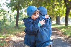 Identical twin brothers embrace each other. Three four year old identical twin boys in the park. They clung to each other. They are dressed in demi-season Royalty Free Stock Photos