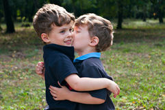 Identical twin brothers embraced each other with a kiss Royalty Free Stock Photos