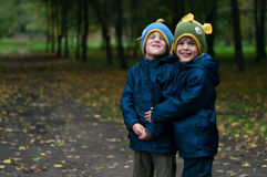 Identical twin brothers embraced with mock expression. Three four year old identical twin boys in the forest. They are dressed in anoraks and knitted hats. They Royalty Free Stock Images