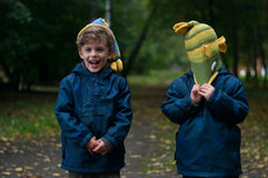 Identical twin brothers joking with the hat. Three four year old identical twin boys in the forest. They are dressed in anoraks and knitted hats. They are Royalty Free Stock Photo