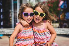 Identical twin girls on summer vacation posing for camera. Royalty Free Stock Photography
