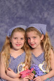 Identical twin sisters holding. Shot of identical twin sisters holding flowers Royalty Free Stock Image