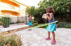 Identical twin sisters are playing on vacation with hula hoop stock photos
