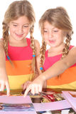 Identical twin sisters putting. Shot of identical twin sisters putting photo's in an album Royalty Free Stock Photography