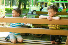 Identical twins on the bench. Three year old boys on the bench. Children dressed in the colours of the Ukrainian flag. Summertime Stock Images