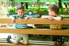 Identical twins on the bench. Three year old boys on the bench. Children dressed in the colours of the Ukrainian flag. Summertime Stock Photo