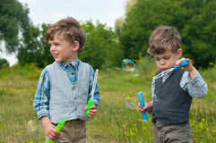 Identical twins blow soap bubbles. Three year old identical twins  blow soap bubbles on the meadow Stock Photo
