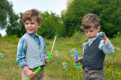 Identical twins blow soap bubbles. Three year old identical twins blow soap bubbles on the meadow Stock Photos