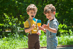 Identical twins with lollipops. Three year old identical twins are holding the candy in the colors of the Ukrainian flag. Summertime royalty free stock images