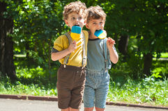 Identical twins with lollipops Royalty Free Stock Photography