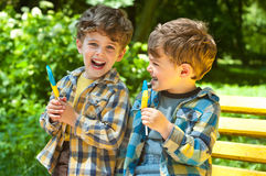 Identical twins with lollipops. Three year old identical twins are holding lollipops in colors of the Ukrainian flag. The children are dressed in plaid shirts Royalty Free Stock Images