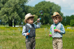Identical twins with soap bubbles Royalty Free Stock Image