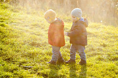 Identical twins for a walk in the meadow. Identical twins stroll on the meadow. They dressed in-between-season garment different colors. Blue and rad jackets Stock Images