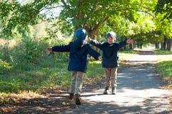 Identieke tweelingdiebroers in werking om worden gesteld om elkaar te omhelzen Stock Foto