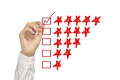 Identificar de verificação da mão do negócio por meio do marcador vermelho em uma avaliação de cinco estrelas Imagem de Stock Royalty Free