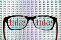 Identification of fake news. Photo depicts glasses in front of the computer screen and serves as a concept of the fake news - to identify false news from a stock image
