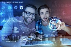 Positive programmer developing a new security programm. Identification profile. Cheerful young programmers working at night while developing new security program Stock Image