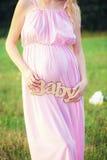 Identifichi il ` del bambino del ` nelle mani di una donna incinta immagine stock libera da diritti