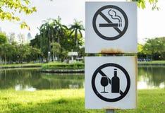 Identifichi non fumatori e sporcando il metallo del segno firmi dentro il parco fotografia stock