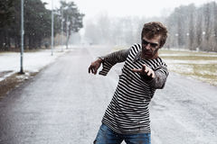 Identifying the victim of the day. Man with a mudded face reaching victim Stock Photo