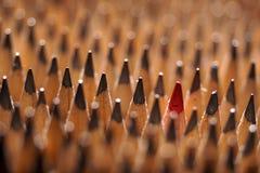 Identische schwarze Graphitbleistifte und ein roter Bleistift Lizenzfreie Stockbilder