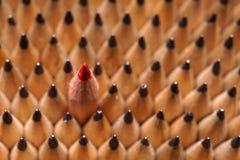 Identische schwarze Graphitbleistifte und ein roter Bleistift Lizenzfreie Stockfotografie