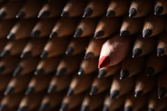 Identiska svarta grafitblyertspennor och en röd blyertspenna Arkivbild