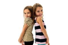 Identiska tvilling- flickor är vänd fasadbeklädnad tillbaka till baksida Arkivbilder