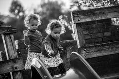 Identiska tvilling- flickor på glidbana på lekplats Royaltyfri Fotografi