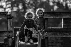 Identiska tvilling- flickor på glidbana på lekplats Arkivfoto