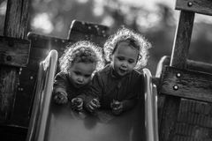 Identiska tvilling- flickor på glidbana på lekplats Royaltyfri Bild