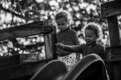 Identiska tvilling- flickor på glidbana på lekplats Royaltyfria Foton