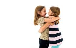 Identiska tvilling- flickor ser de och att le Arkivfoton