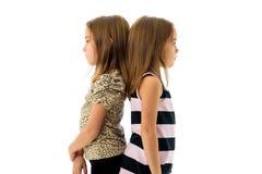 Identiska tvilling- flickor vänds tillbaka till baksida som är ledsen Arkivfoto