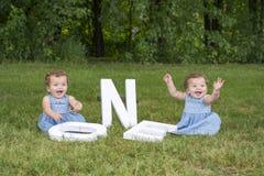 Identiska tvilling- systrar som sitter i gräset Royaltyfri Fotografi