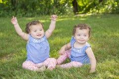 Identiska tvilling- systrar som sitter i gräset Fotografering för Bildbyråer